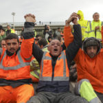 epa07182529 More than one hundred dockers from the port of Setubal block the entrance of a bus that transports the workers who will replace them by loading a ship with vehicles from the Autoeuropa factory, Portugal, 22 November 2018. Workers from the port of Setubal have been on strike since 05 November to demand a collective agreement. They had promised a peaceful protest, but when the bus arrived they prevented the passage.  EPA-EFE/RUI MINDERICO